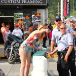 Officers protecting-and-serving a young lady in body paint, Sturgis Rally 2015