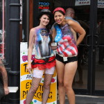 Ladies on Sturgis Main Street advertising for a tattoo parlor in body paint